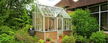 Front View of a White Hartley Botanic Bespoke Lean To Glasshouse With Brick Base.