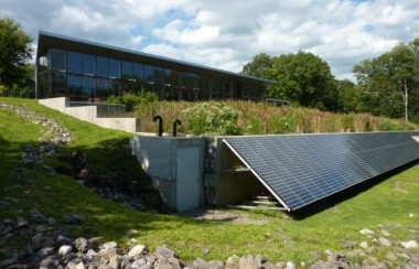 exterior-of-greenhouse-with-constructed-wetlands-and-solar-panels-in-foreground